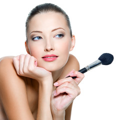 woman  holds the make-up brushe for applying  rouge