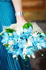 Woman holding beautiful azure wedding flowers bouquet