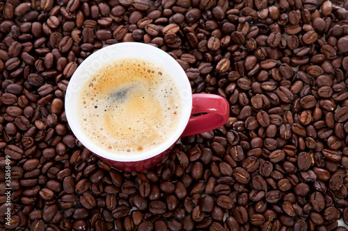 coffee cup in background of beans