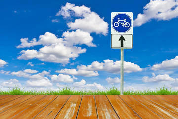 wood bicycle way and sign against blue sky