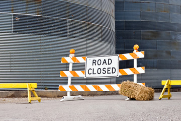 Road closed sign in front of silos