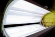 Open tanning bed with lit white bulbs