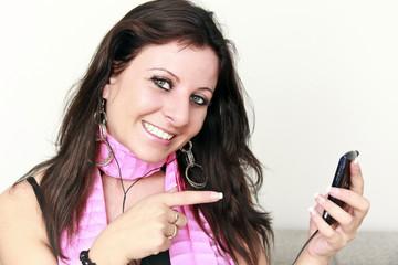 lächelnde, junge Frau zeigt auf ihr Mobiltelefon