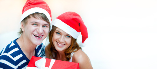 Young happy couple in Christmas hats standing together and holdi