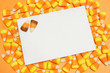 Blank greeting card on a cluster of Halloween candy corn