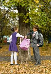 Школьник помогает однокласснице донести портфель