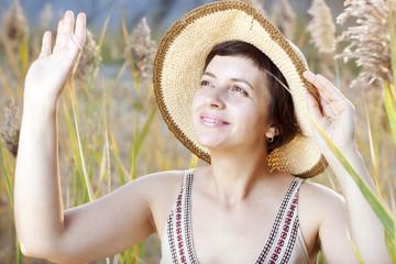 Portrait of beautiful brunette woman in summer reed