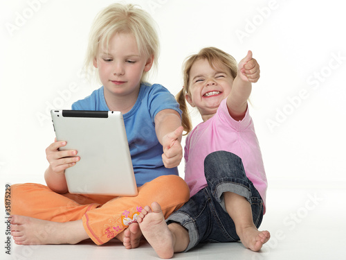 Adorable little girls seated on the floor playing with touchpad