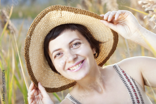 Portrait of beautiful brunette woman in summer reed