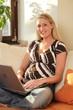 Junge Frauliest mit Laptop