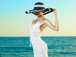Leinwandbild Motiv Elegant woman in a hat at sea