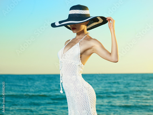 Canvas Akt Elegant woman in a hat at sea
