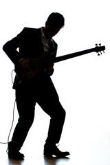 A bass guitar player in a suit