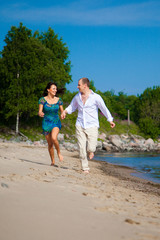 Enamored man and girl running along coast of sea