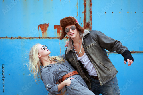 Urban couple swinging pose on grunge background