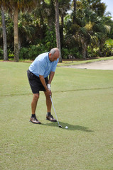 man putting on a golf course