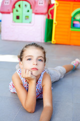 beautiful little serious girl lying on floor