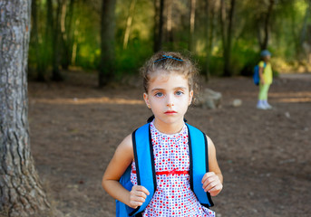 Children girl hiking with backpack in forest