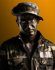 young soldier face with jungle camouflage on a yellow background