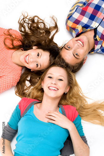 Three young friends lying down