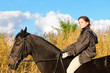 Pretty girl riding horse and look at view front of reed