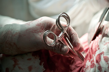 Hands of the surgeon With Clamp