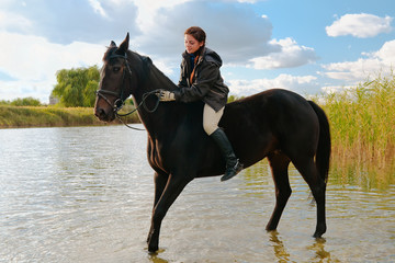Pretty girl riding horse in shallow river water