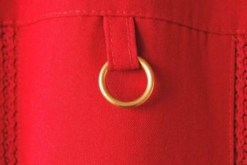 Goldener Schmuckring mit Lasche - Detail einer roten Bluse
