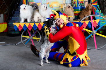 Smiling clown embraces his dog
