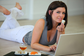 Woman lying on the floor eating sushi and surfing the internet