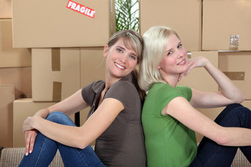 twosome of young girls moving in together sitting back-to-back