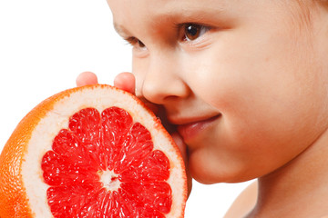 Little boy with a juicy pink grapefruit