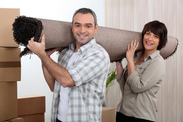 Couple carrying carpet over shoulders