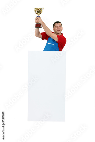 Man standing behind a blank sign and holding a trophy
