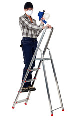 craftswoman on a ladder holding a sprayer and wearing a mask