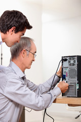 Father and son repairing PC