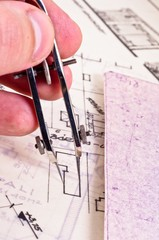Fingers of an architect drawing a new home
