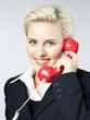 Portrait of a beautiful female with red  telephone handset