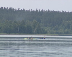 Canoes passing fast into a lake filmed from lake shore.