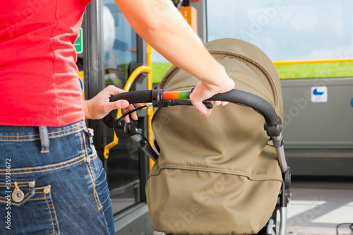 Woman with stroller getting into a bus