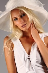 Sexy blonde girl in a white skirt wearing a white hat