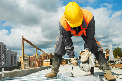 builder working with cutting grinder - 35937002