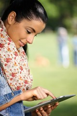 Pretty girl using tablet outdoors smiling