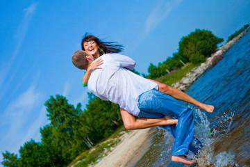Enamored couple embracing on sunny beach