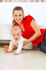 Happy mother and lovely baby playing on floor