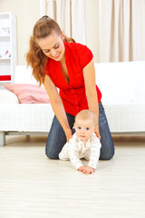 Smiling mother helping cheerful baby learn to creep