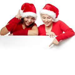 Pretty girls with santa hat showing something on copyspace
