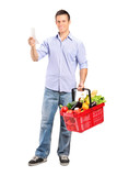 Man looking at store receipt and holding a shopping basket poster