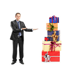 Portrait of a man in suit gesturing and pile of gifts