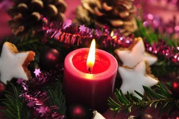 Kerze mit Zimtsternen und Tannenzapfen